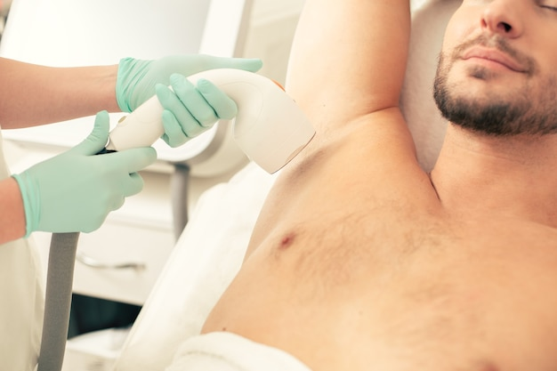 Close up of the man having his underarm hair removed during the laser hair removal procedure