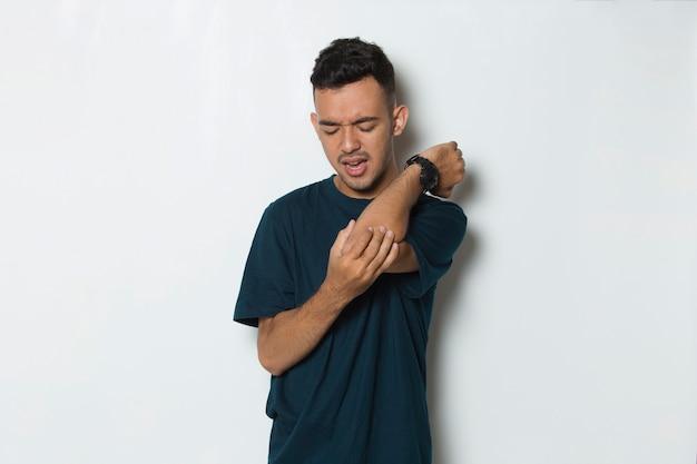 흰색 배경에 격리된 부상당한 팔꿈치와 팔에 통증이 있는 남자를 닫습니다