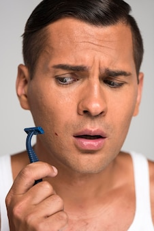 Close-up man having shaving cut