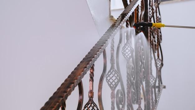 Close up of man in hazmat suit spraying chemical on balustrade inside block ladder against coronavirus.