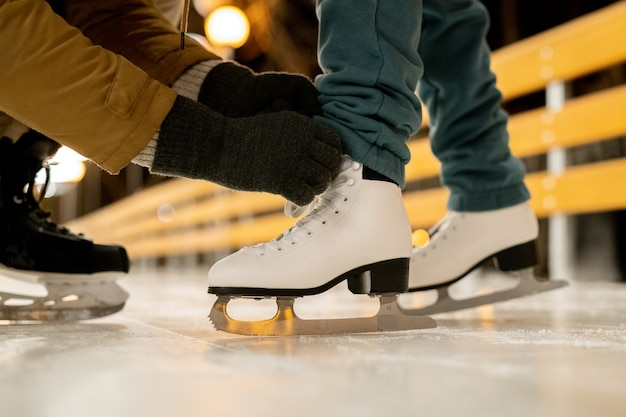 Close-up of man helping his girlfriend to tie shoelaces on figure skates before skating