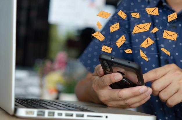 携帯電話を持っているクローズアップの男アイコンの電子メールメッセージ。顧客に情報を送信したり、オンライン取引をハッキングしたりするマーケティングビジネス。ビジネスコンセプトテクノロジー。