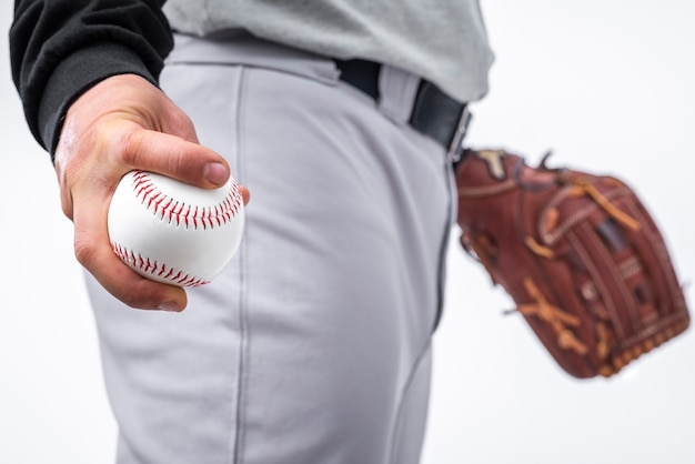 Close-up of man holding baseball and glove