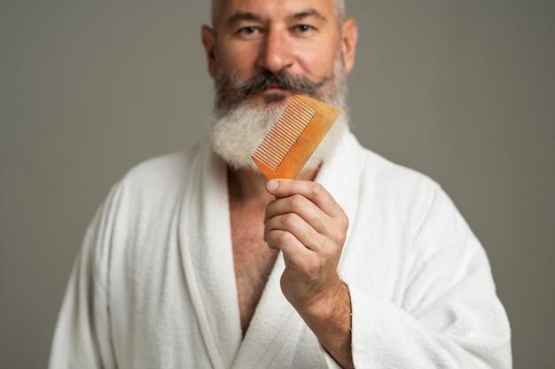 Primo piano uomo che tiene il pettine per la barba