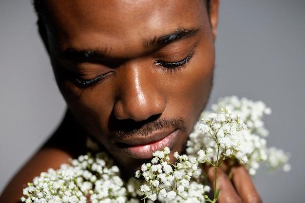 美しい花を持っているクローズアップの男