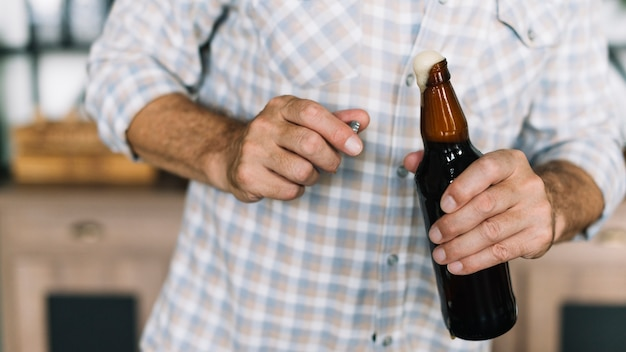 Close-up of man holding beer bottle being opened with froth