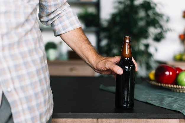 Close-up of a man holding beer bottle on kitchen counter