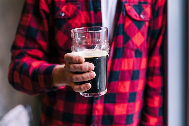 Close-up of man holding beer glass in hand