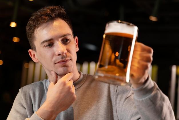 Uomo del primo piano che tiene boccale di birra