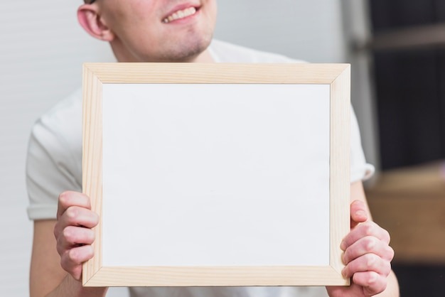Close-up of a man holding blank white picture frame in front of camera