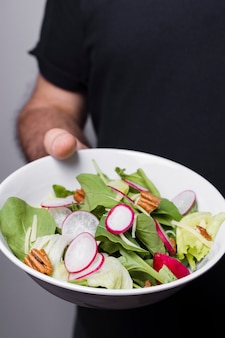 Close-up of man holding bowl of salad