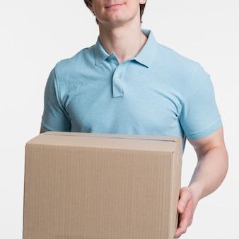 Крупным планом мужчина держит коробку