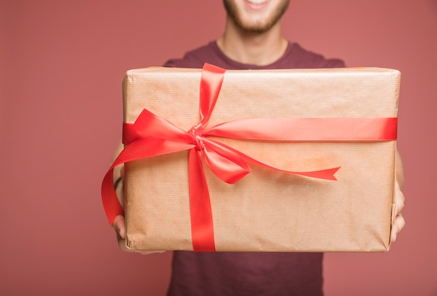 Close-up of man holding brown paper wrapped gift box with red ribbon bow