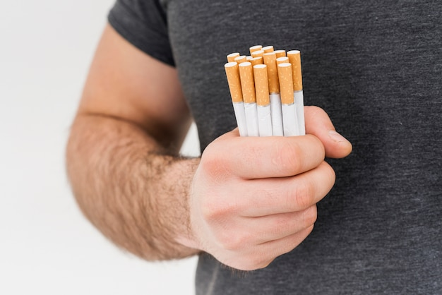 Close-up of a man holding bundle of cigarette isolated on white background