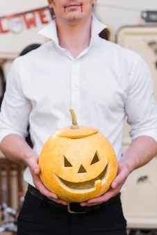 Close-up man holding carved pumpkin