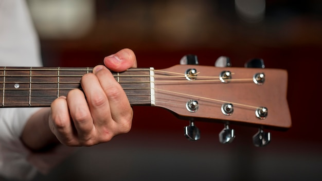Close-up man holding a chord on guitar