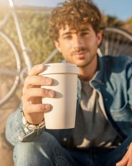 커피 컵을 들고 남자를 닫습니다