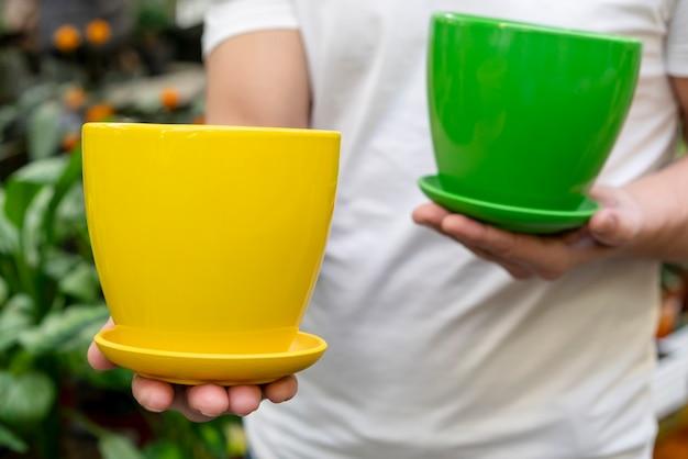 Uomo del primo piano che tiene i vasi da fiori variopinti Foto Gratuite