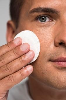 Close-up man holding cotton pad