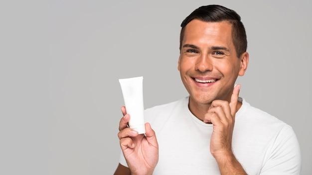 Close-up uomo che tiene il contenitore di crema