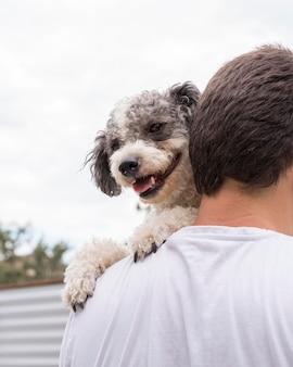 Крупным планом мужчина держит милую собаку