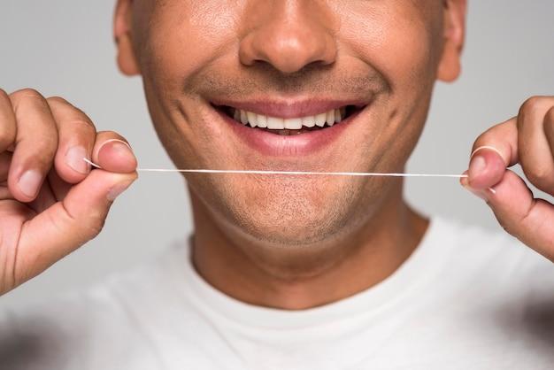 Close-up man holding dental floss