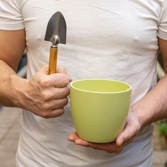 Close-up man holding flower pot and gardening tools