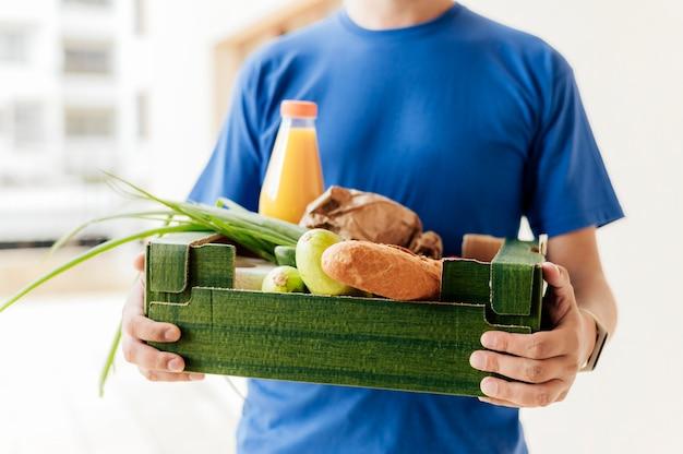 Крупным планом мужчина держит ящик с едой