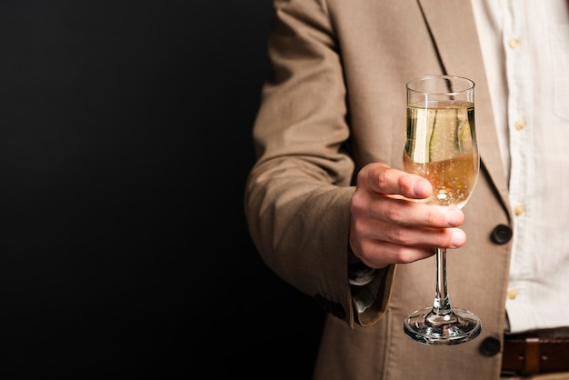 Close-up of man holding glass of champagne with copy-space