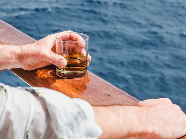 Close up man holding a glass of whiskey