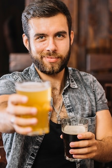 Close-up of a man holding glasses of beer and rum