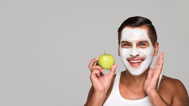 Uomo del primo piano che tiene mela verde