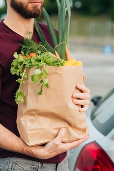 Close-up man holding grocery bag