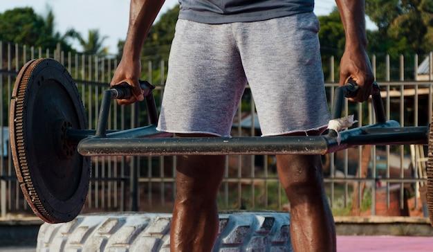 Крупным планом мужчина держит тяжелый вес