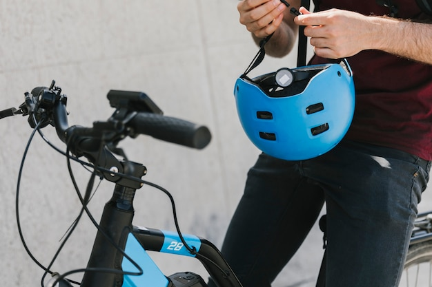 Close up man holding helmet on bicycle