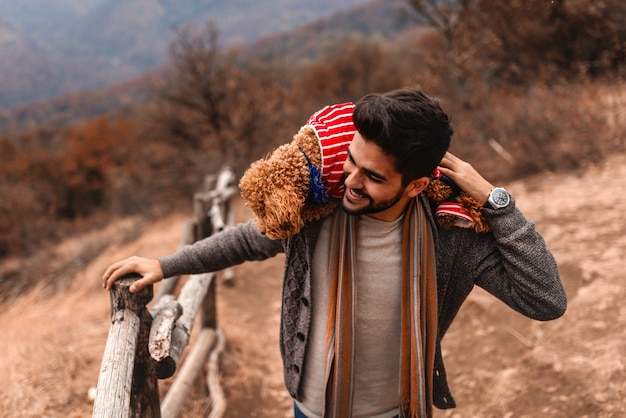 Close up of man holding his dog on shoulders while enjoying nature. autumn time.