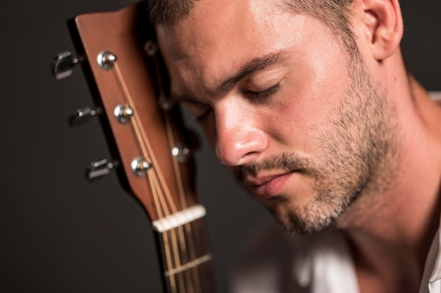 Close-up man holding his head on guitar headstock