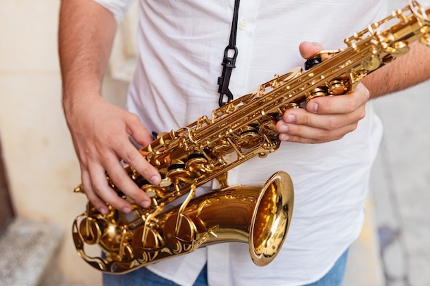 Close up of a man holding his saxophone on the street