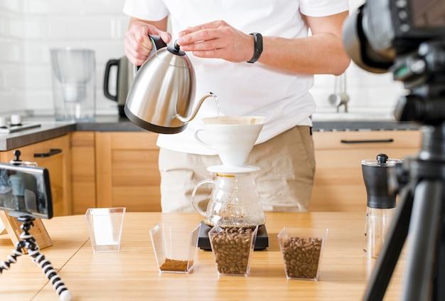Крупным планом мужчина держит чайник