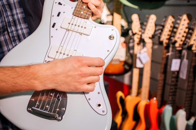 Close up of man holding light-blue guitar in hands