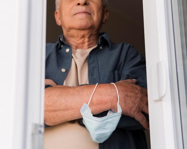 Крупным планом мужчина держит маску на руке