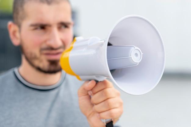 Крупным планом мужчина держит мегафон