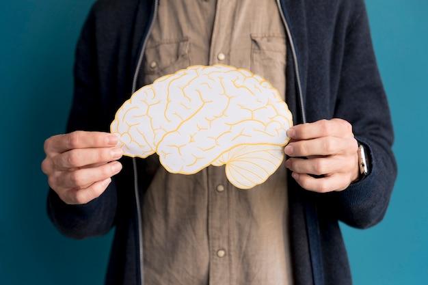 Close-up man holding paper brain