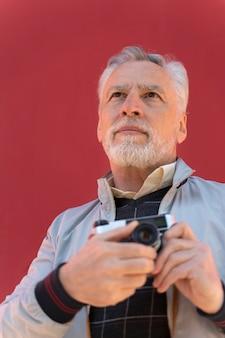Крупным планом мужчина держит фотоаппарат