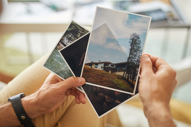 Close-up of man holding photos with beautiful landscapes in his hands