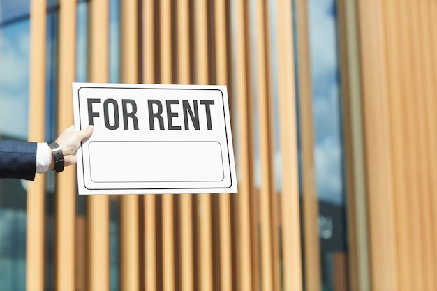 Close-up of man holding placard for rent against the office building outdoors