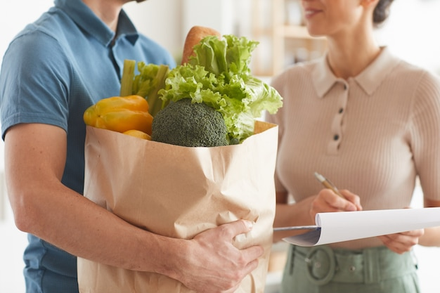 Close-up of man holding products in his hands and delivering food to woman
