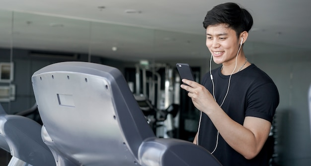 Close up man holding smartphone for playing while walking on treadmill machine