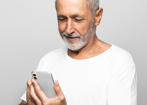 Uomo del primo piano che tiene smartphone