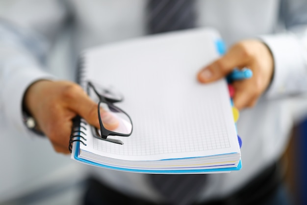 Close-up of man holding stack of business papers.